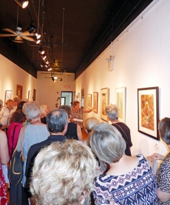 Juror Sue Stuller leads visitors on a tour of the exhibit